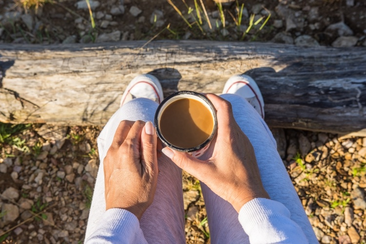 Adult woman is enjoying morning coffee in nature